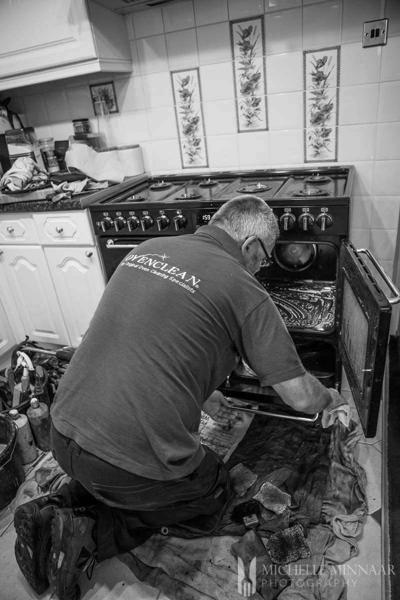 A man cleaning on oven after making goat's cheese and beetroot tart