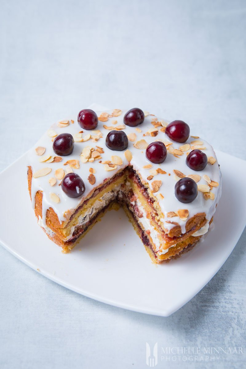 A slice cut out of the cherry bakewell cake
