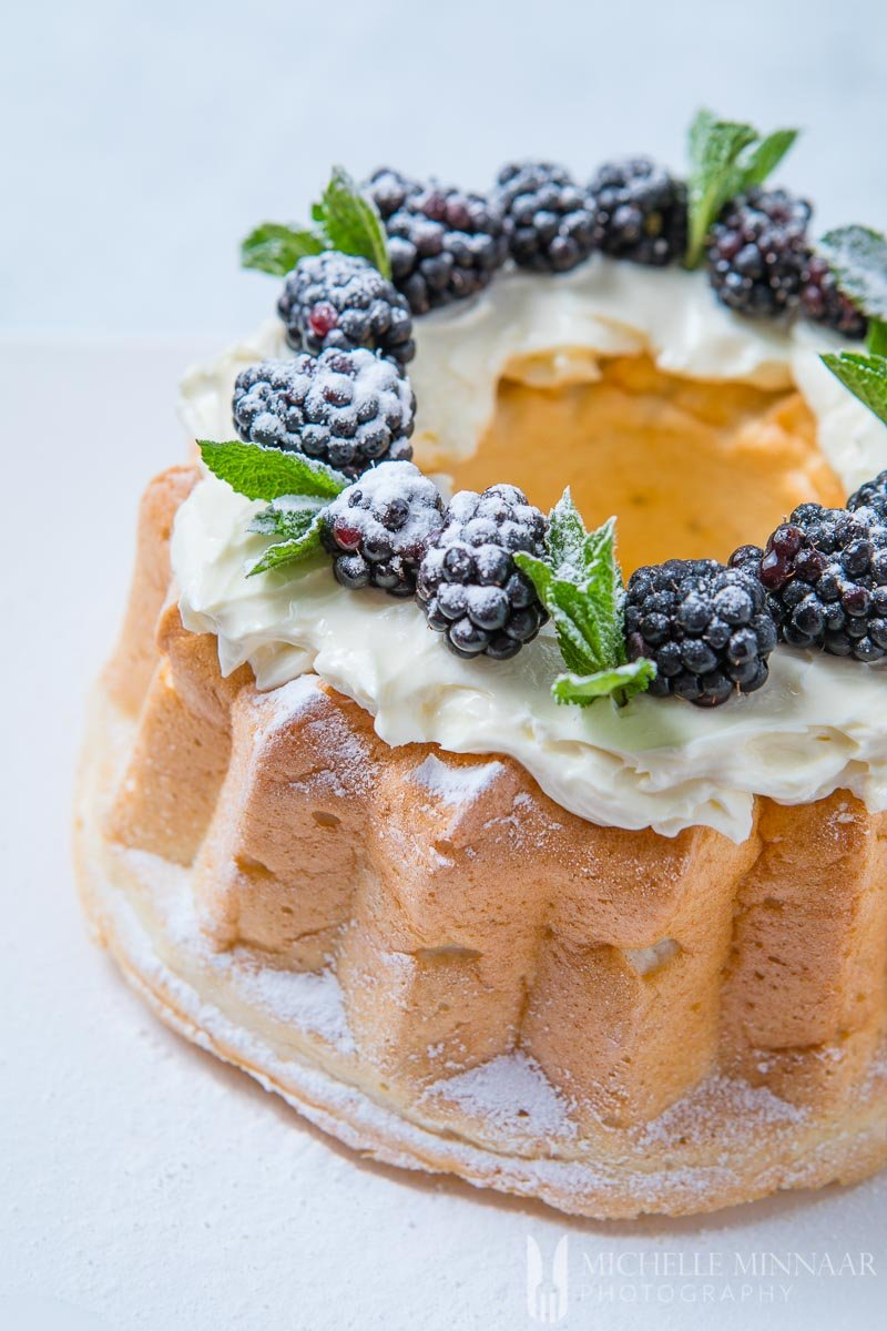 A sugar free angel food cake topped with blackberries and powdered sugar