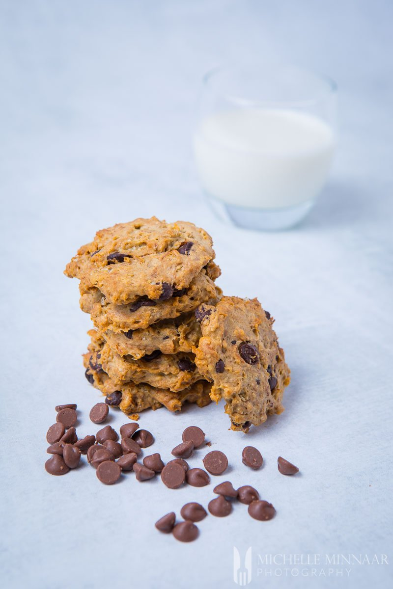 A tall stack of sugar free chocolate chip cookies and chips and milk