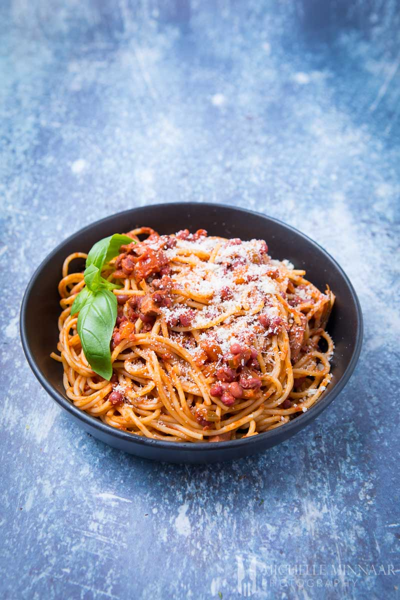 A bowl of vegan spaghetti bolognese, spaghetti with a red sauce and beans