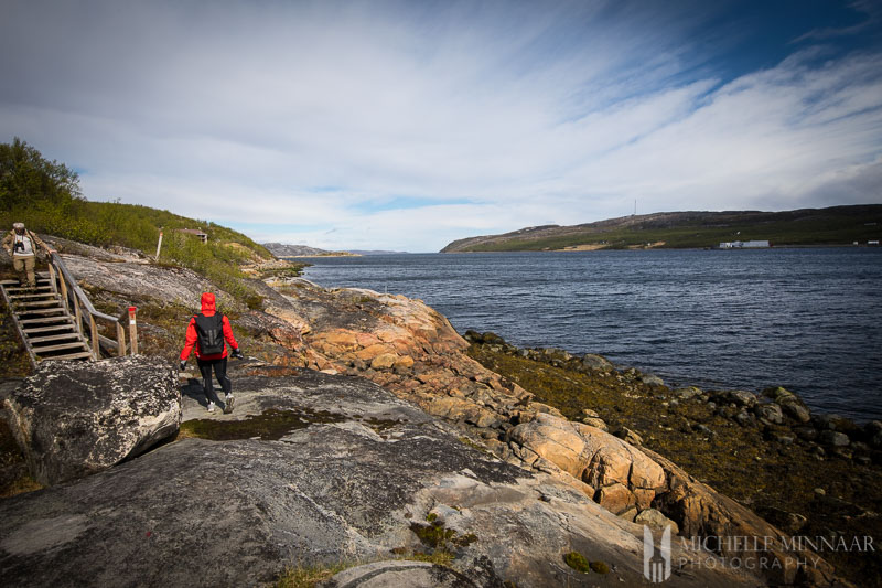 A man walking along the coast of Norway