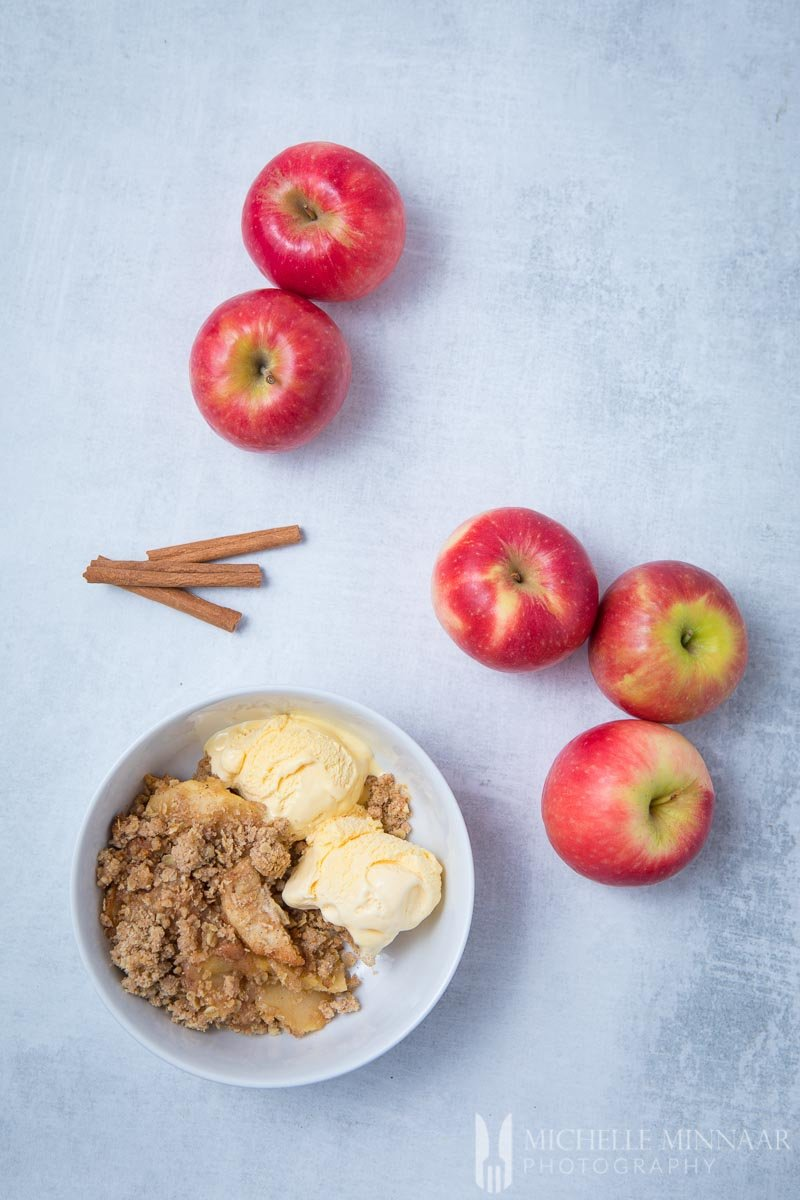 A finished bowl of sugar free apple crisp with whole apples and cinnamon sticks on a counter