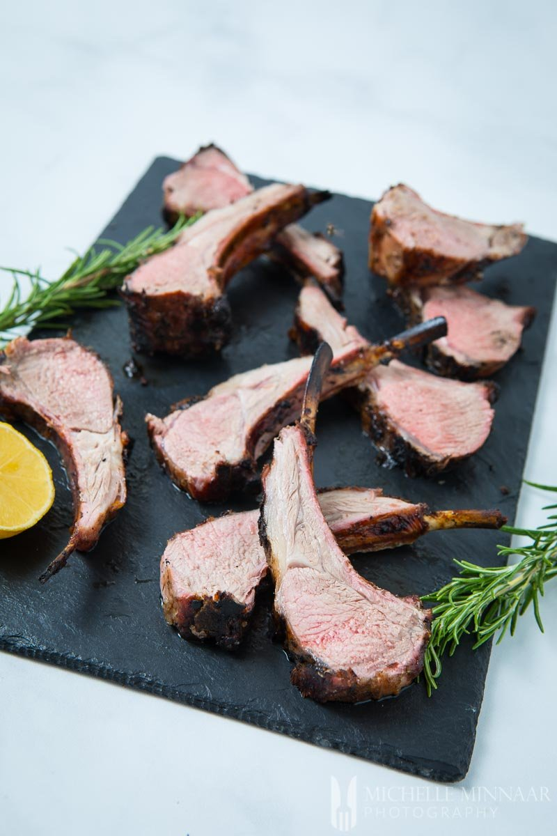 Lamb Chops on a marble slab with a lemon
