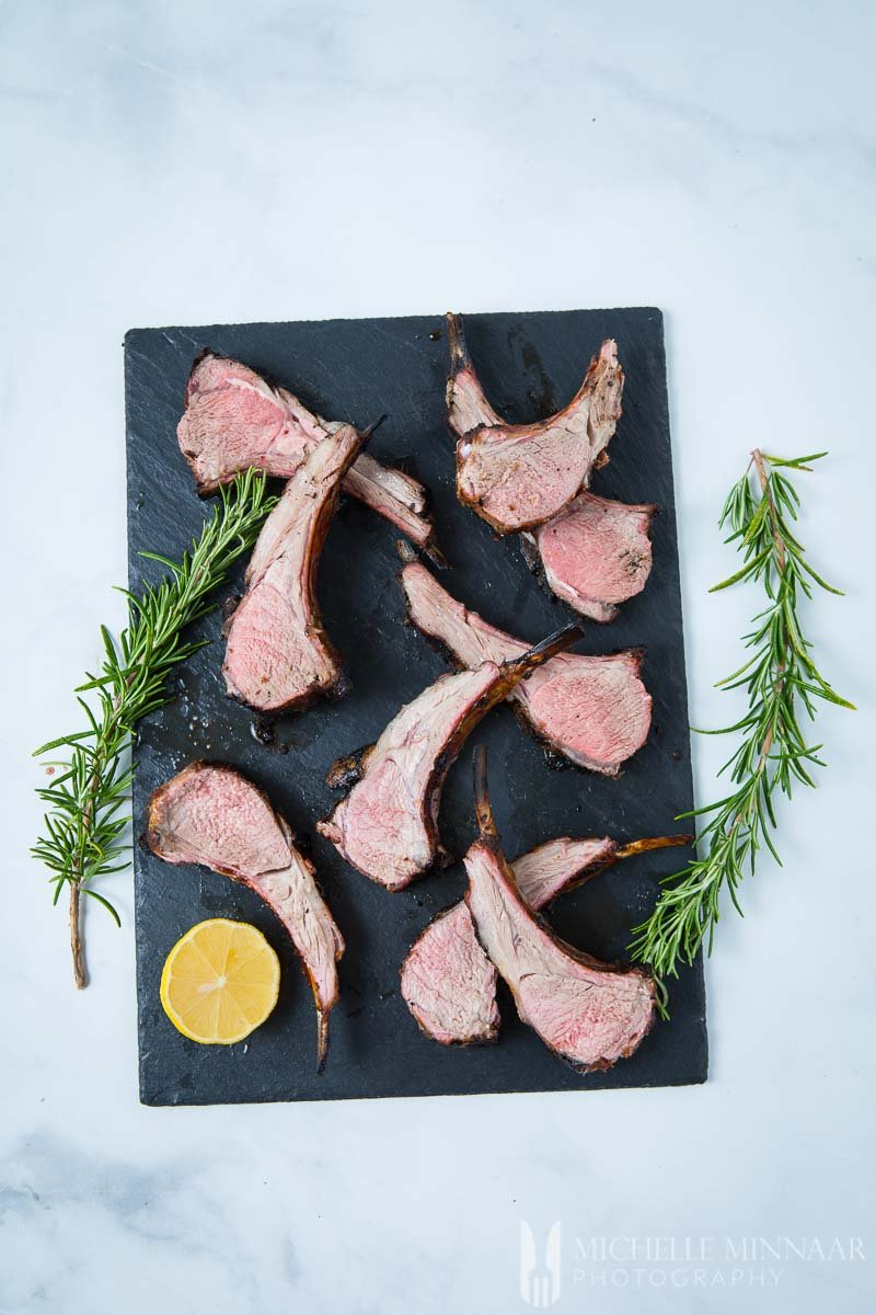 BBQ rack of lamb on a grey slab with rosemary sprigs
