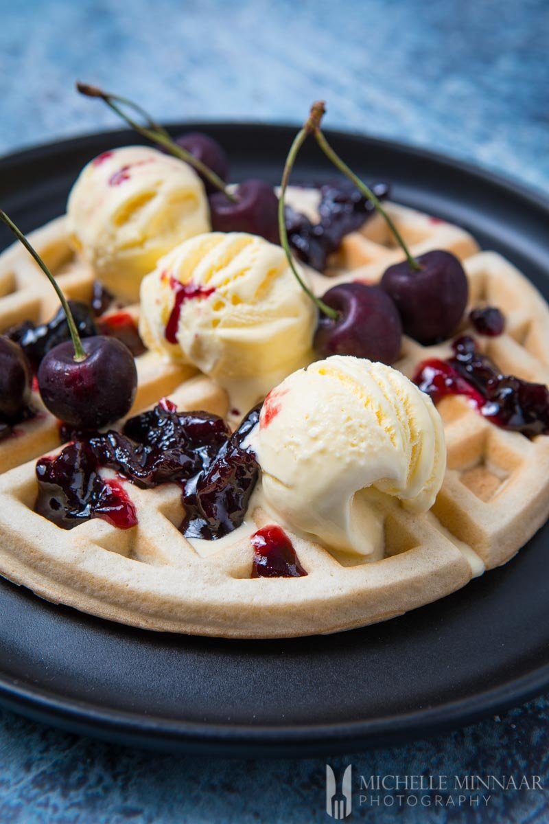 A close up of dairy free waffles with ice cream and cherries on top