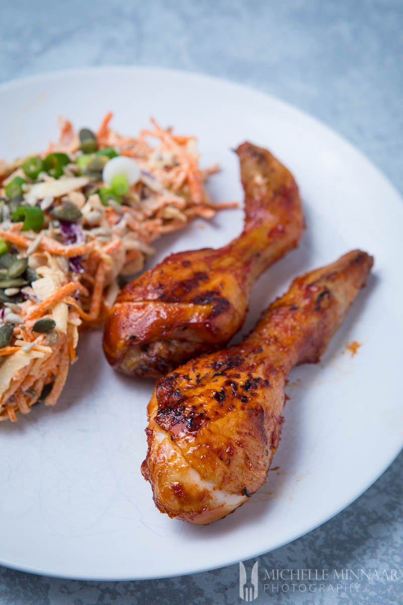 Some bbq chicken on a plate with coleslaw
