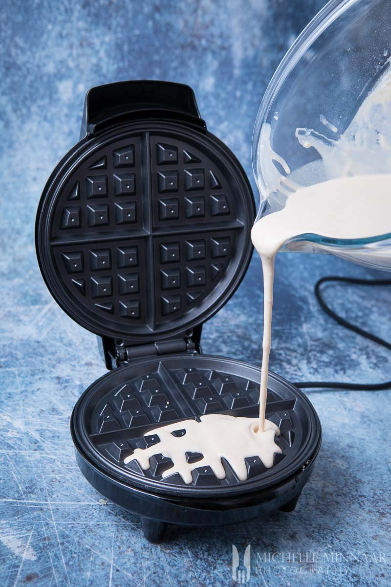 Batter being poured onto a waffle iron