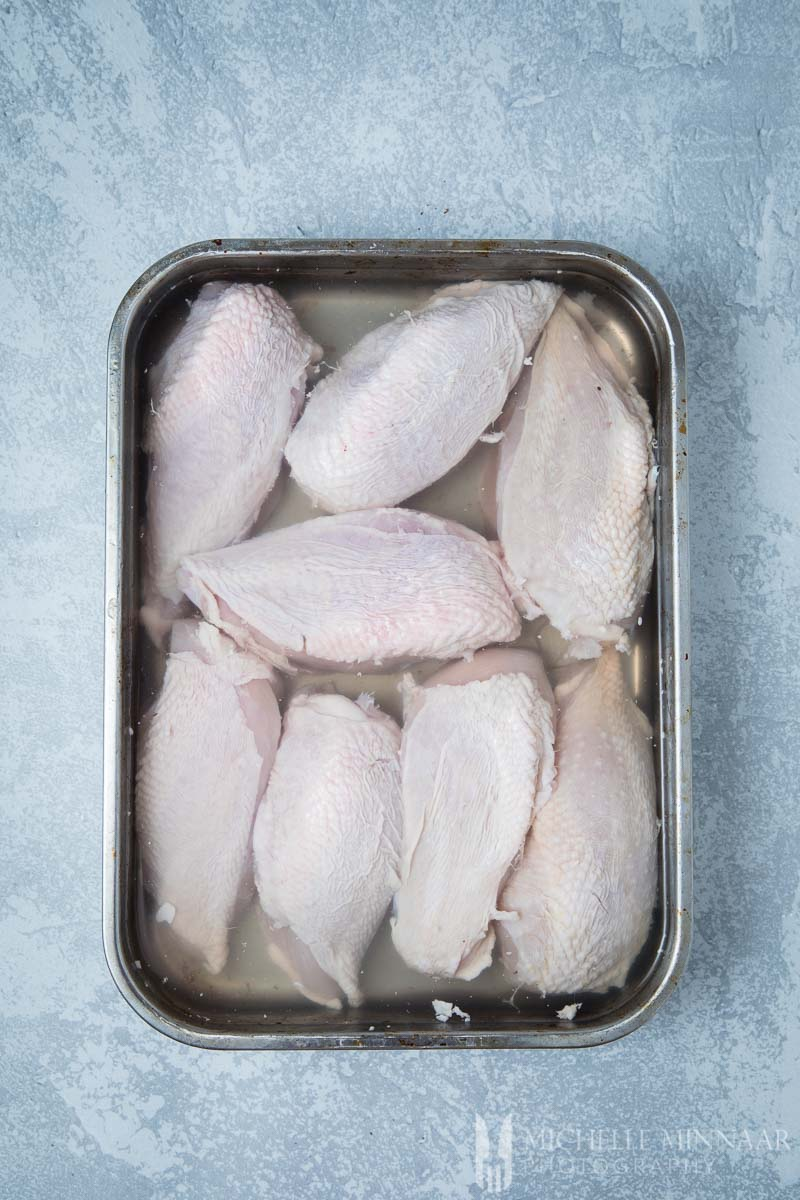 Raw chicken breasts in brining liquid in a pan