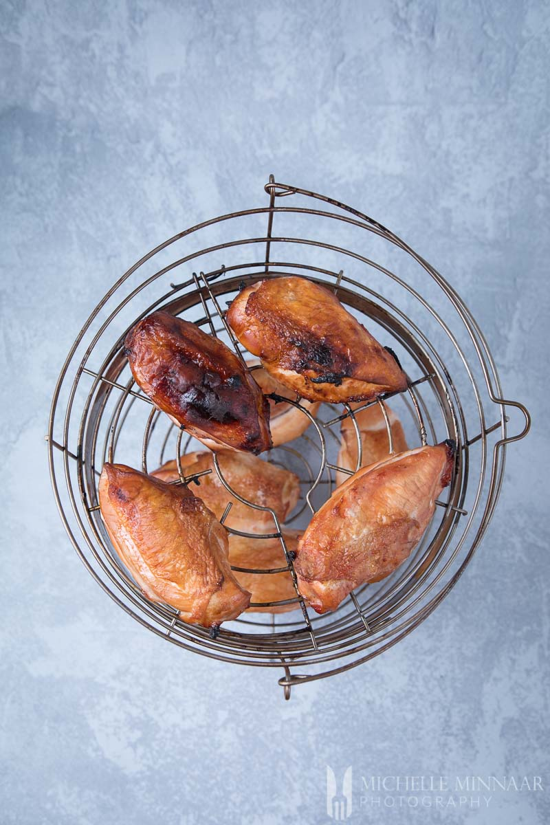 A wire basket full of smoked chicken breasts