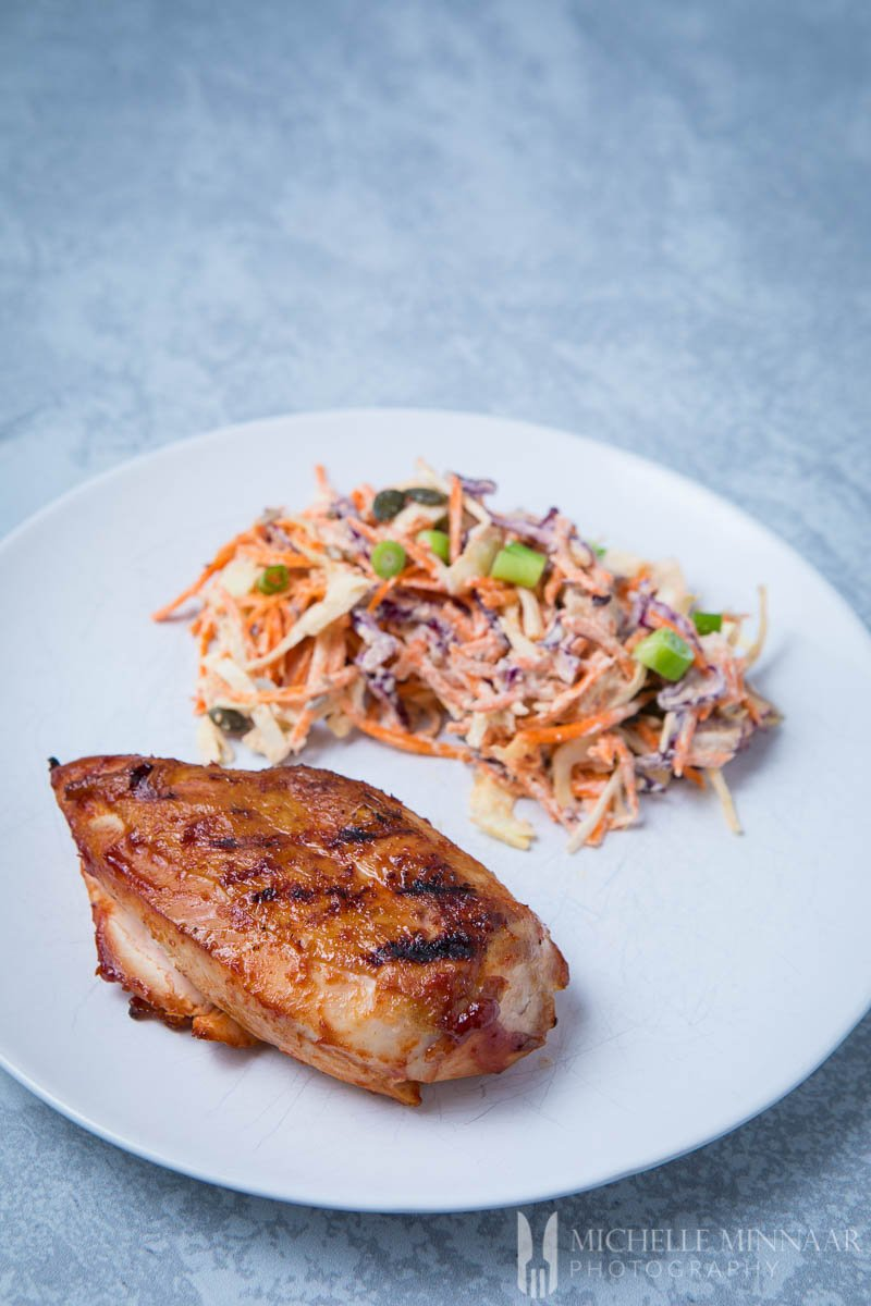 A brined chicken breast and vegan coleslaw on a white plate