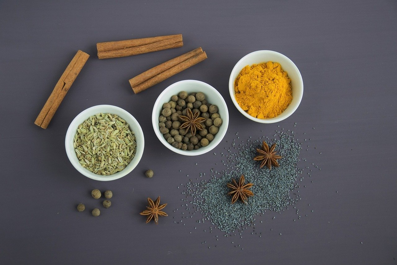 Three bowls of spices and anise seeds around them