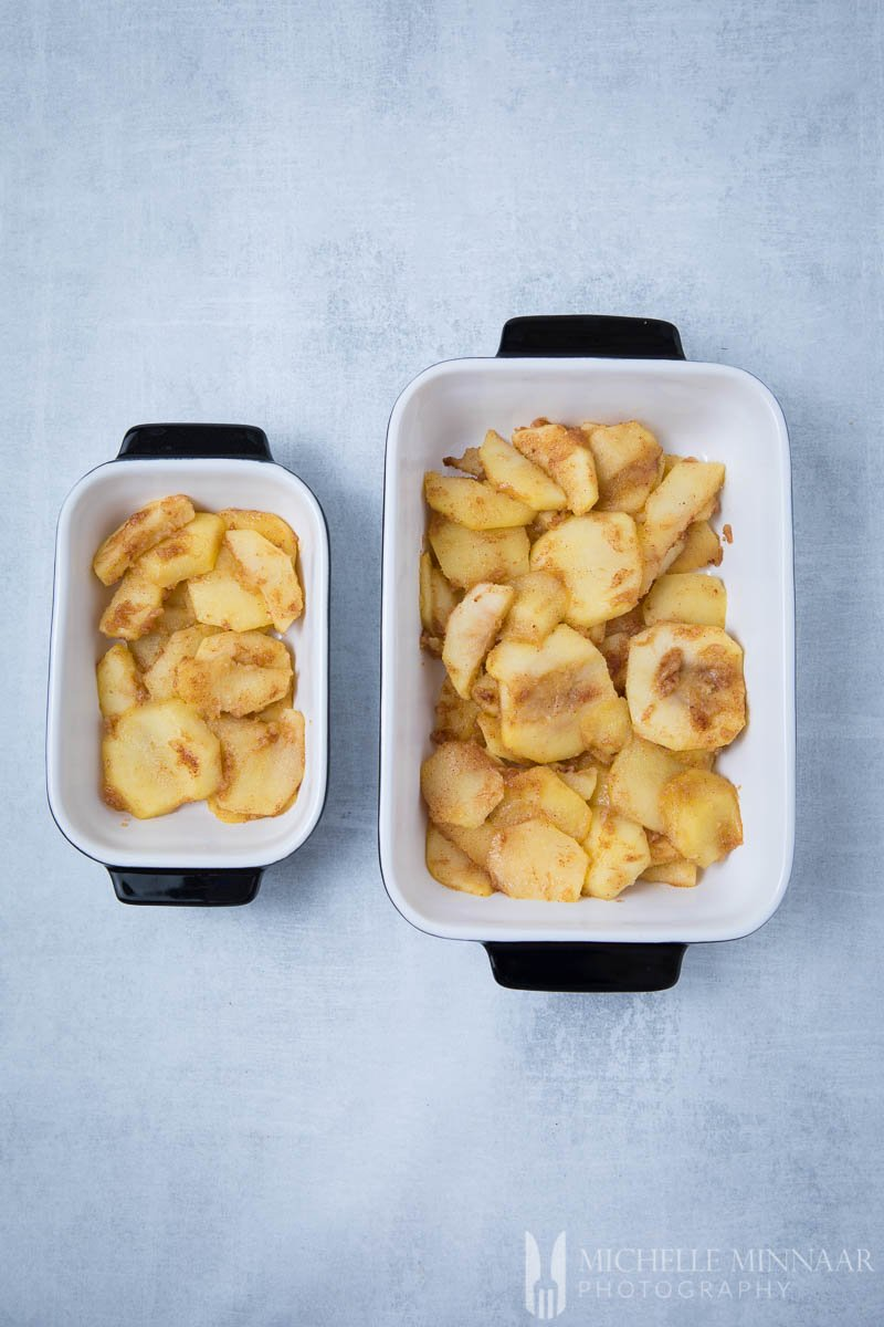 Baked apples in two white pans to make sugar free apple crisp