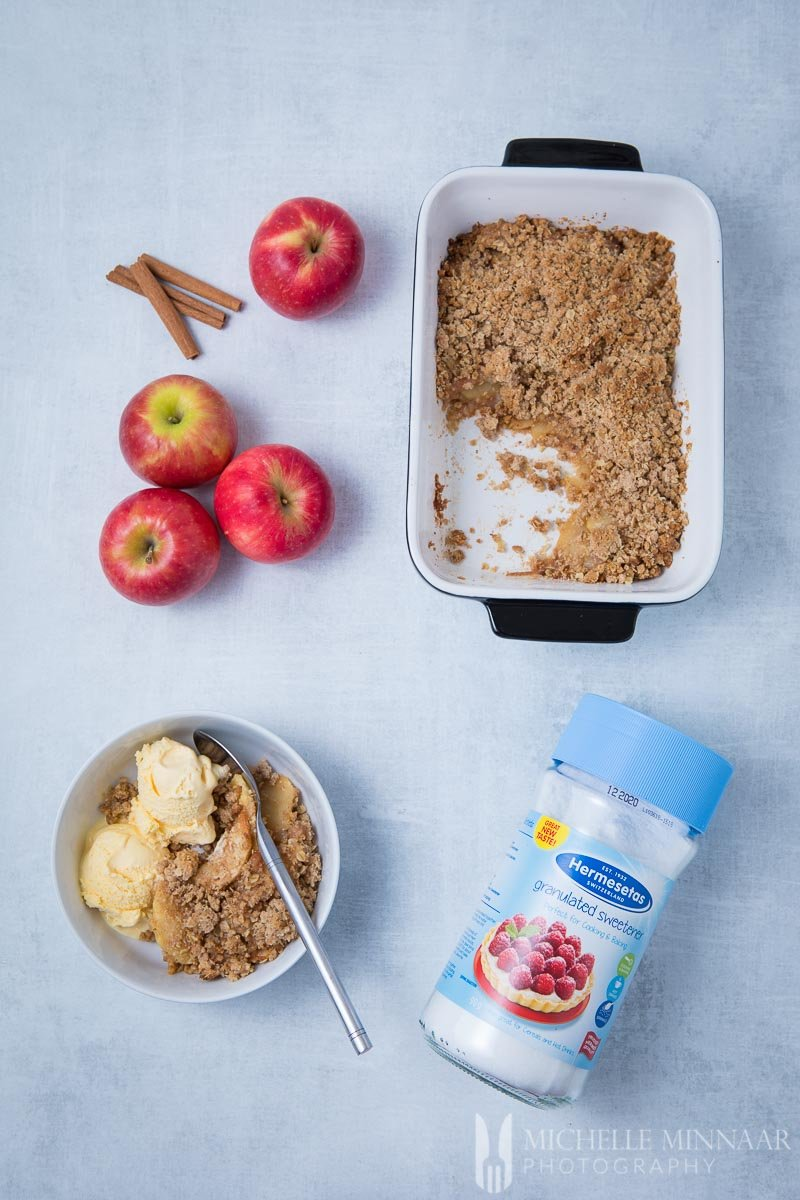 A bowl of sugar free apple crisp with a pan with a chunk of the pie out of it