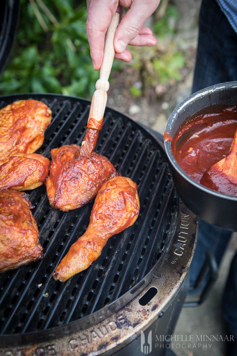 Chicken Drumsticks being sauced with bbq sauce on a grill