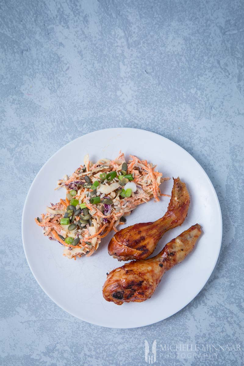 brined chicken drumsticks and coleslaw on a plate