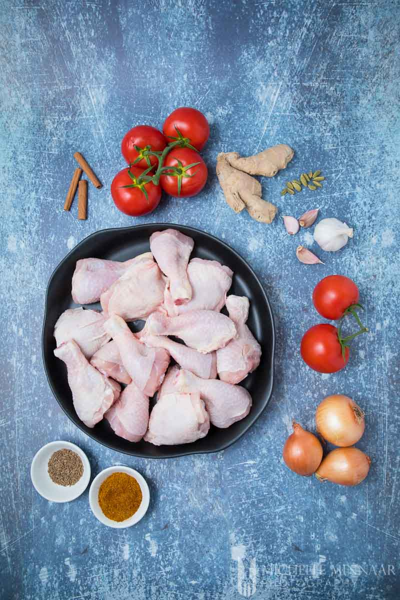 Ingredients for Chicken Kasha - raw chicken in a bowl, spices, onions, tomatoes