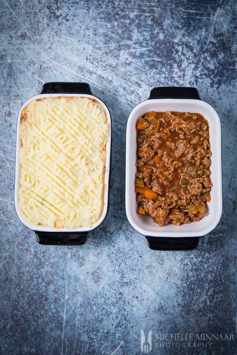 Two dishes of gluten free shepherd's pie, one with the mash on top and the other without it