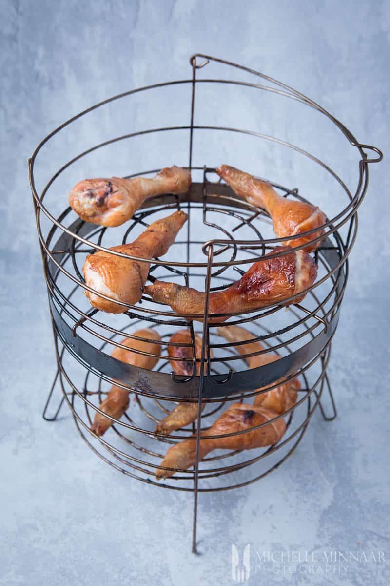 Smoked chicken drumsticks in a wire basket