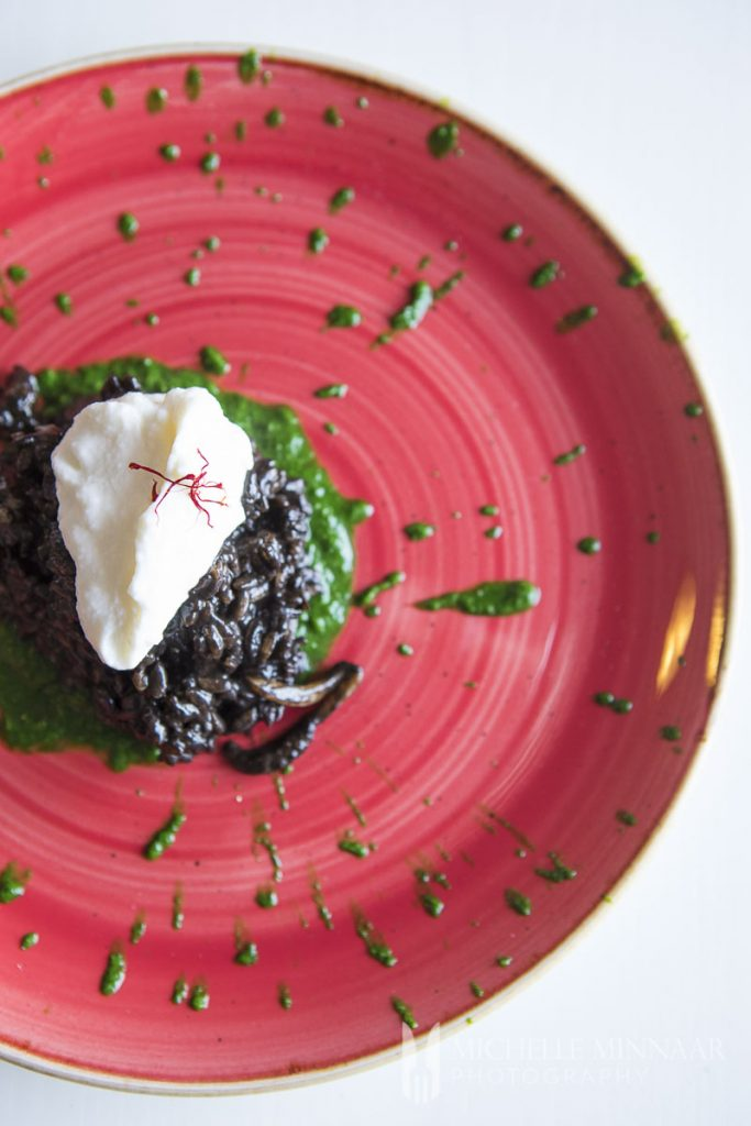 A pink plate with black risotto with a white dollap of sauce on top