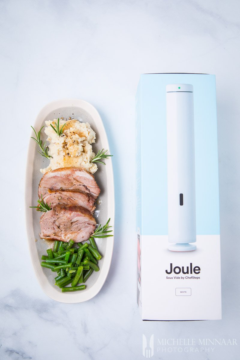 A plate of sous vide lamb shoulder with greens beans next to the Joule box
