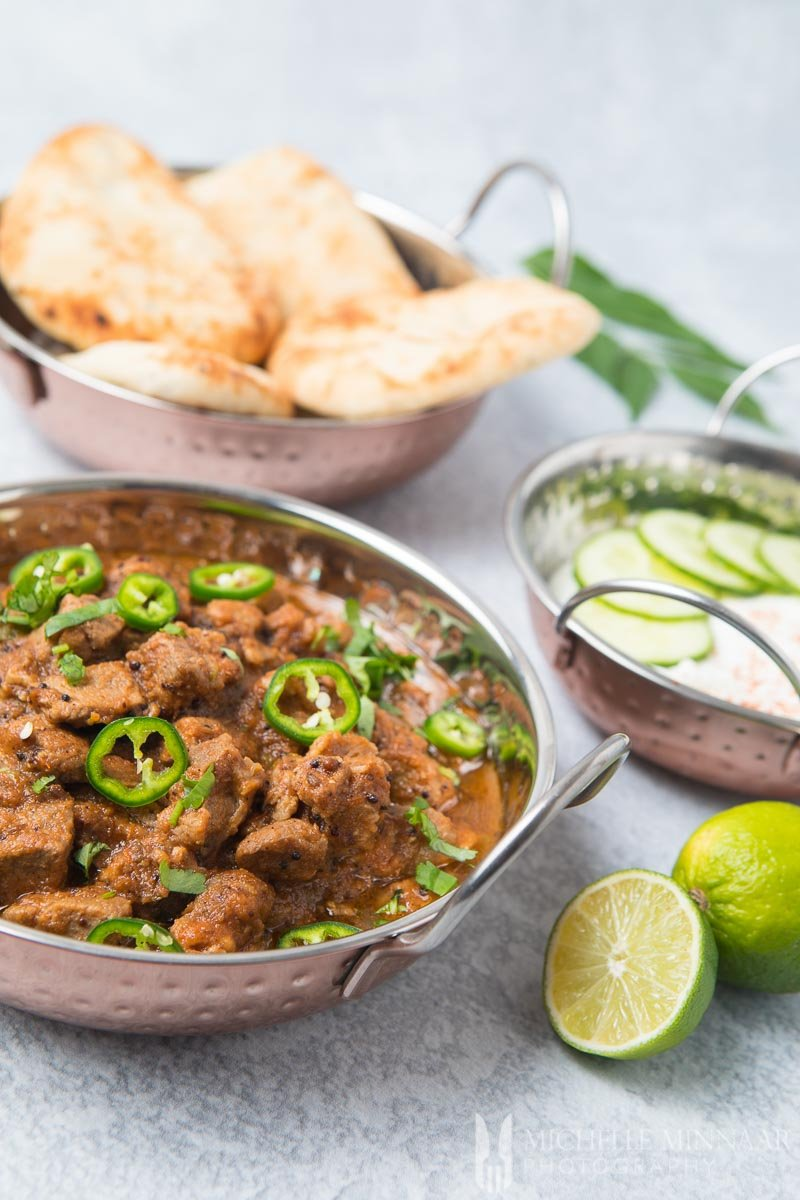 A close up of lamb bhuna in a silver bowl