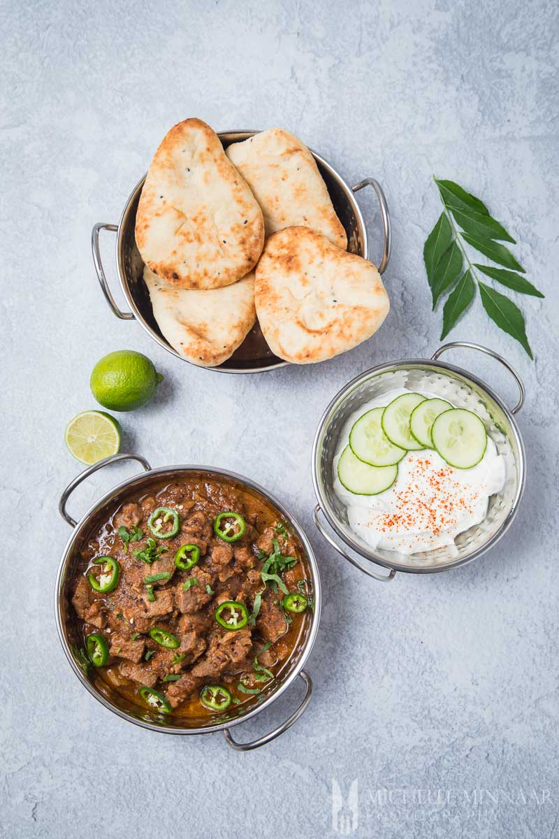 An indian meal, lamb bhuna, naan and raita