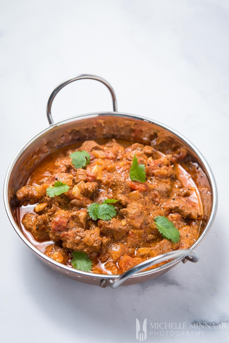 A bowl of browned lamb with a brown sauce in a silver pan for Lamb Madras