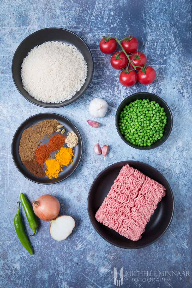 Ingredients to make Keema Rice: Ground beef, spices, peas, tomatoes, white rice