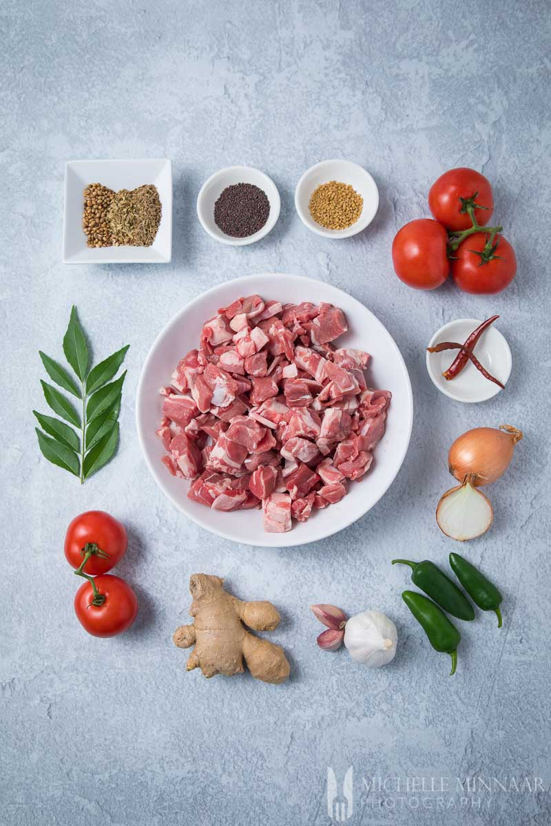 Ingredients to make lamb bhuna: raw lamb, tomatoes, garlic, peppers, ginger and onions