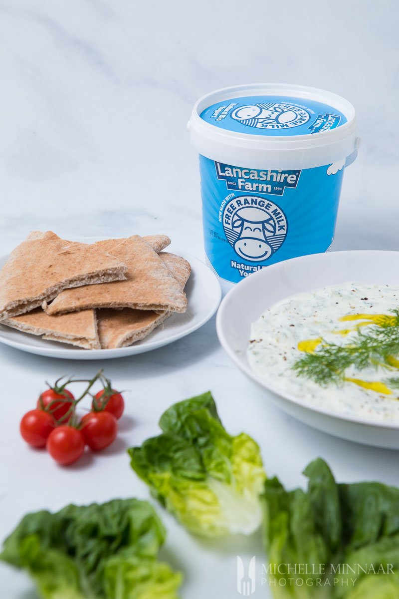 Pita bread, yogurt and cacik on a counter