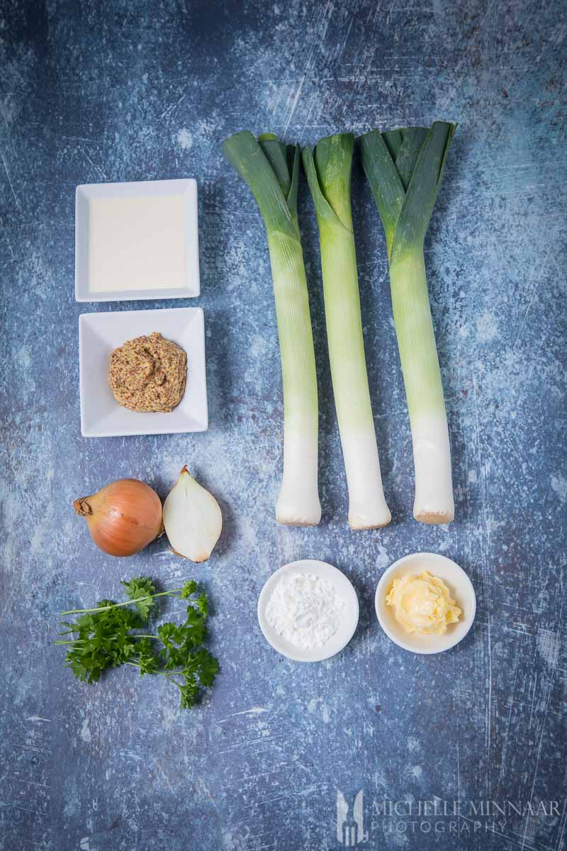 Ingredients for mustard soup: Mustard, Cream, Flour, Onions, Parsley, Leeks on a counter