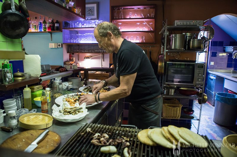 A man creating the seafood platter in the kitchen of t' kleine oestertje