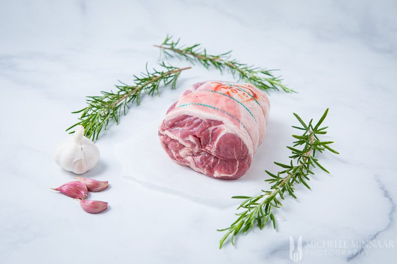A raw rack of lamb and rosemary and garlic on a counter