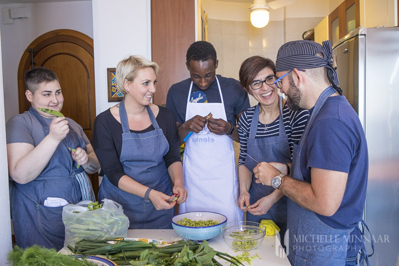 Five chefs standing around a table cooking squid ink risotto
