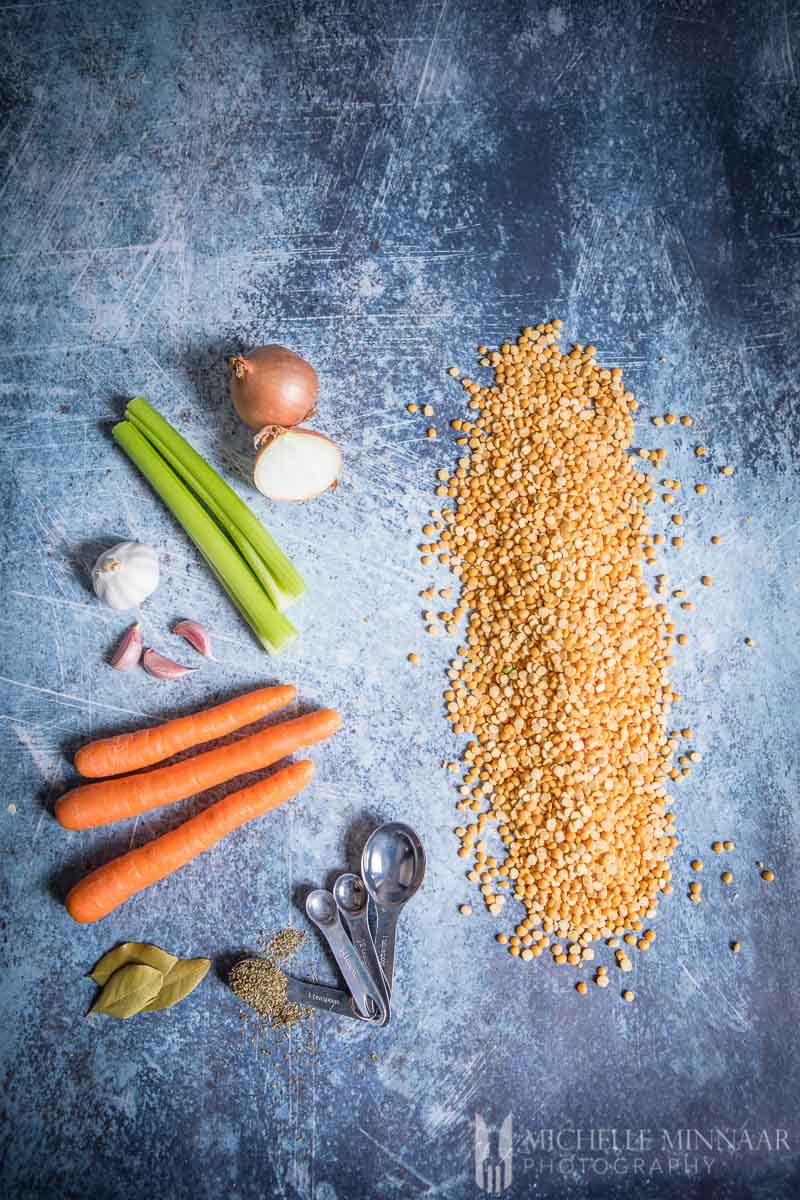 Ingredients to make vegan split pea soup on a counter: Celery Carrot Onion Split Peas