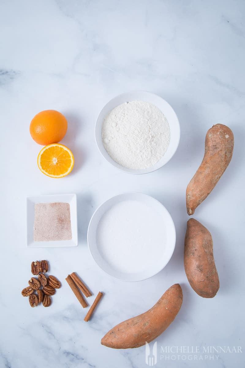 """Ingredients to make vegan sweet potato pancakes """" orange, flour, sugar, sweet potatoes"""