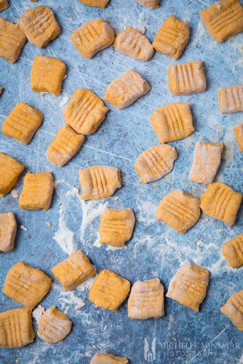 A close of of raw vegan sweet potato gnocchi cut into sqaures