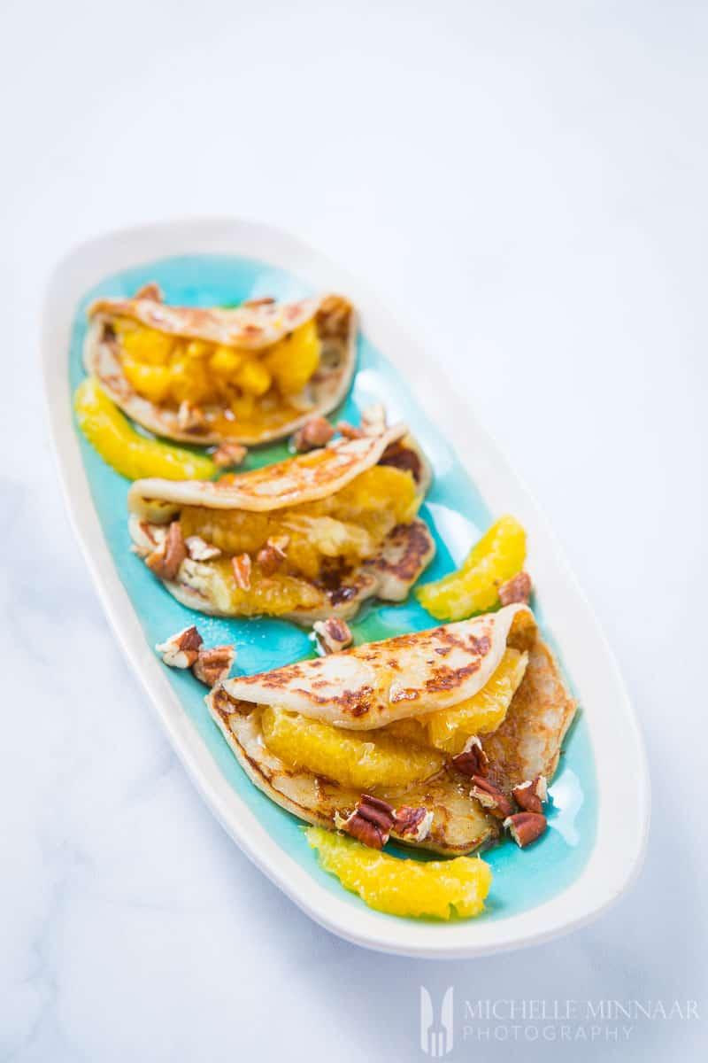 A close up of folder vegan sweet potato pancakes stuffed with peaches and walnuts