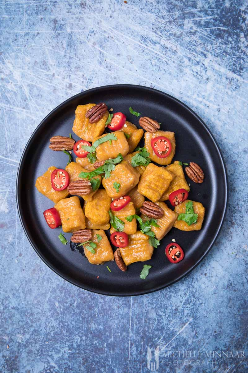 A bowl of vegan sweet potato gnocchi with tomatoes and nuts as garnish