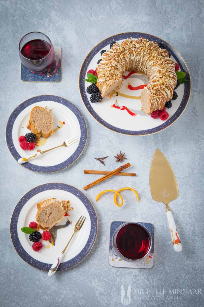 Glasses of wine with pieces of cinnamon bundt cake on plates