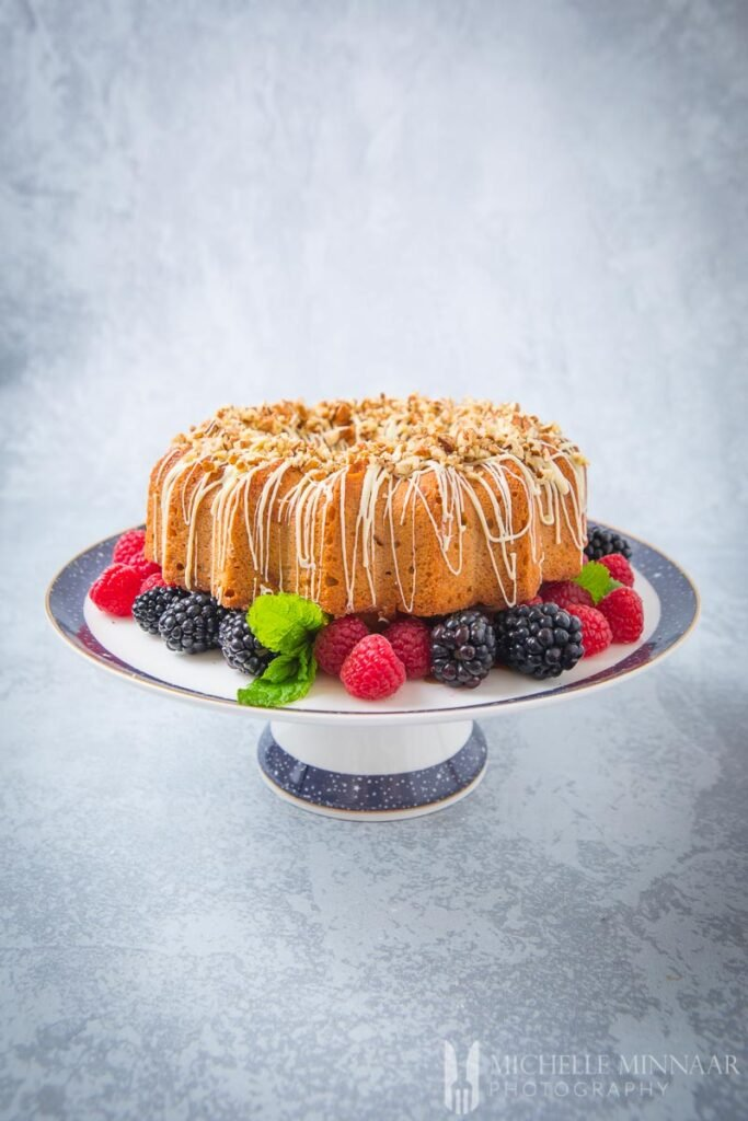 A brown bundt cake on a platter with berries underneath