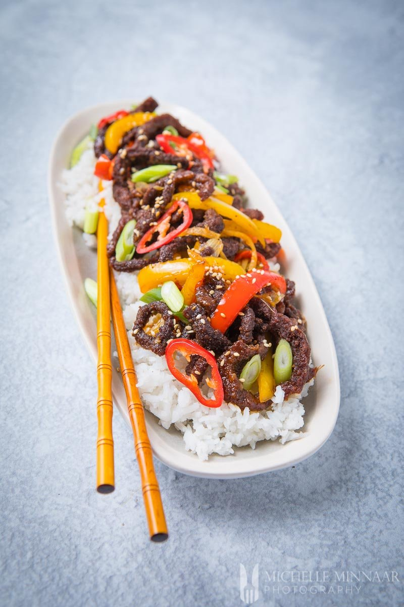 A plate of crispy chilli beef on top of white rice with chop sticks