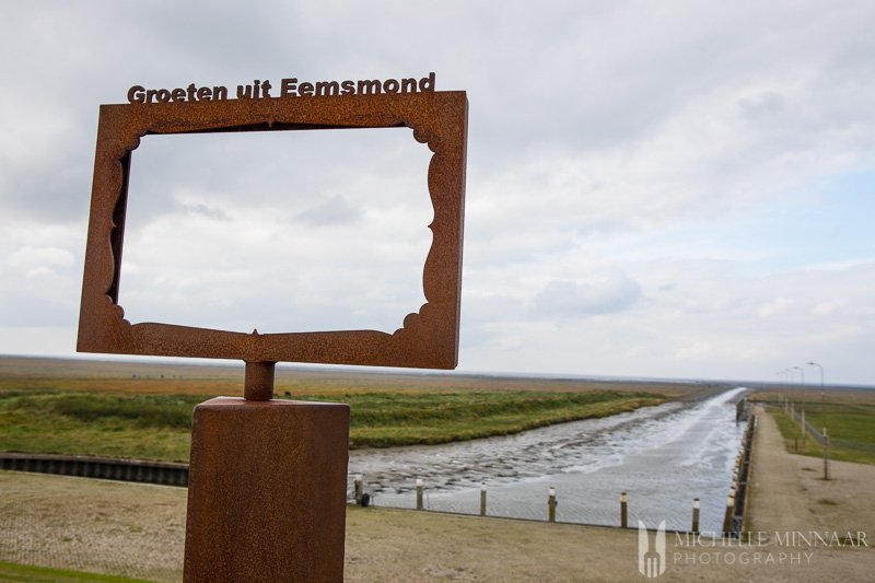 A brown sign with a river in the background