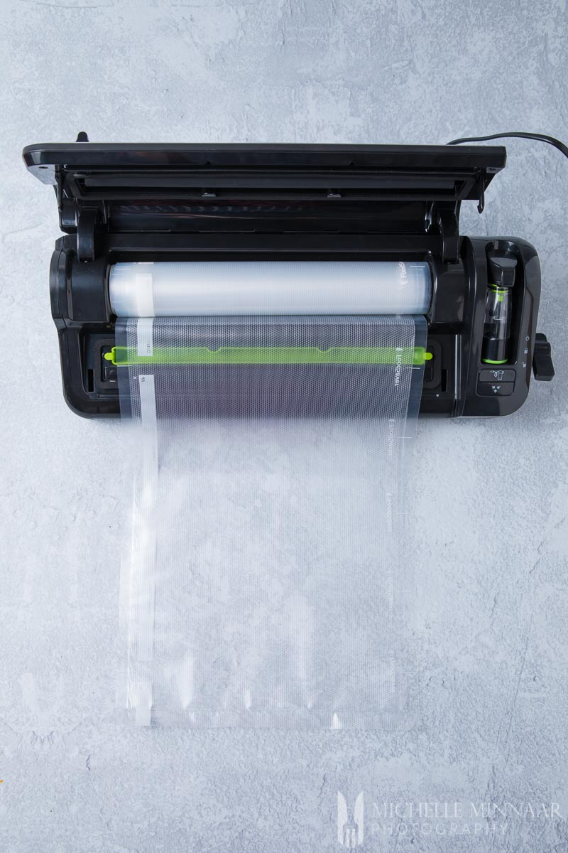 A foodsaver vacuum sealer and a plastic bag coming out of it