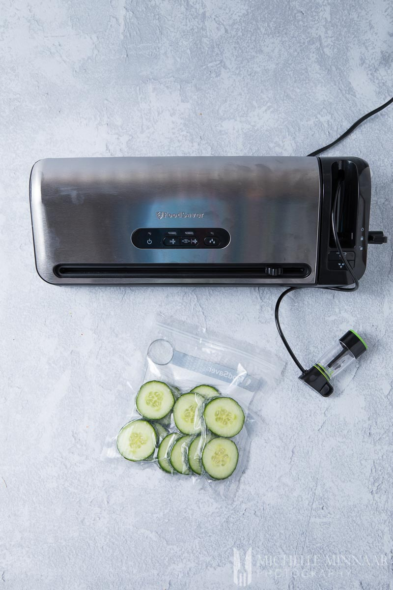 A vacuum sealer and a bag of cucumbers