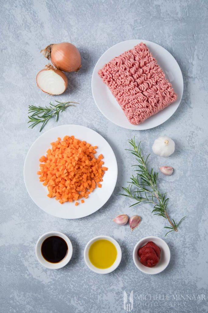 Ingredients to make lamb mince: raw lamb, carrots, onions, garlic