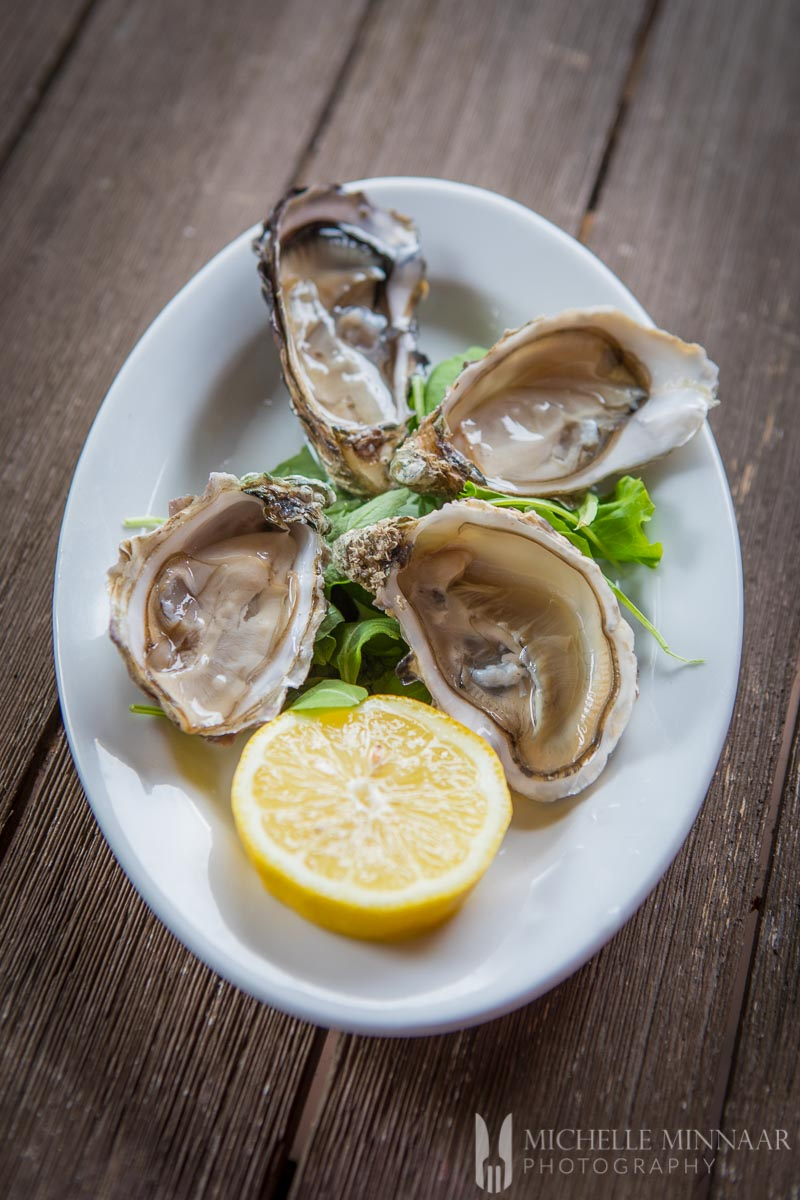 Four oysters on a plate with a lemon wedge