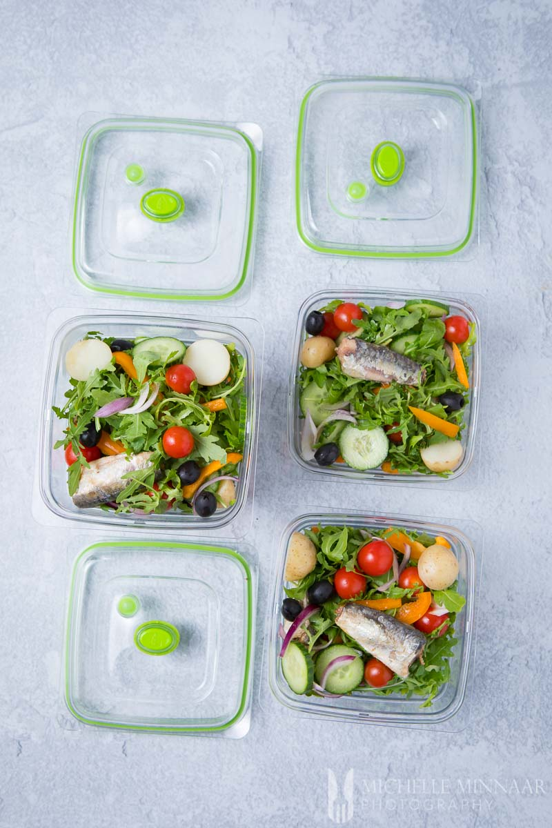 Three salad containers with sardines and salad in them