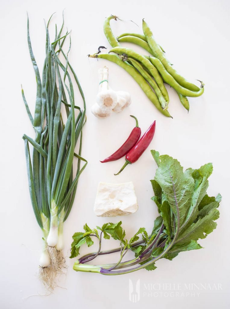 Ingredients to make macco di fave: spring onions, peppers, gralic, green beans